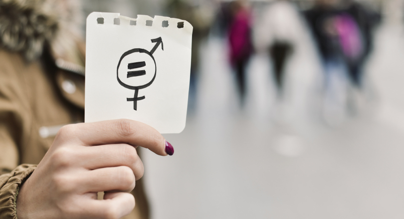 A woman holding up a symbol for gender equality