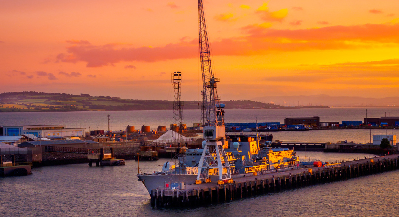 Rosyth at sunset with naval vessel moored